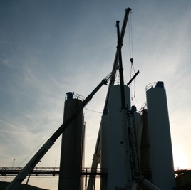 Three cranes rigging silos